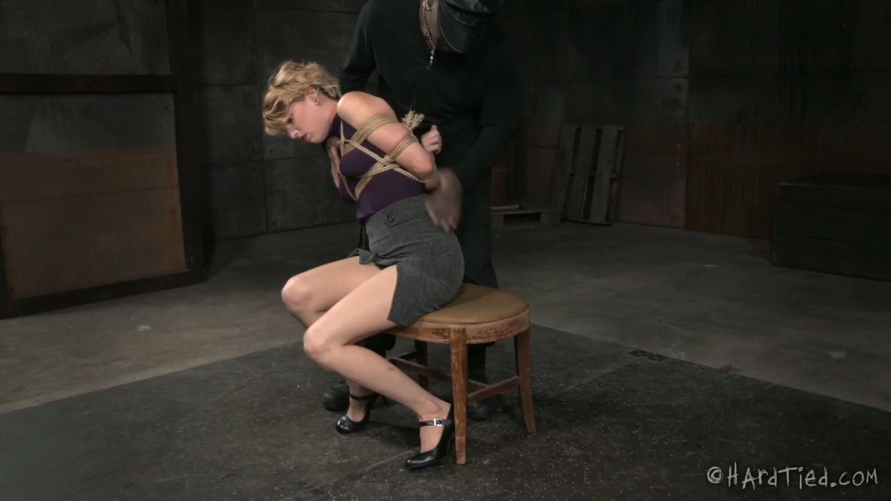 Beautiful blonde lady is tied up in standing pose in BDSM video